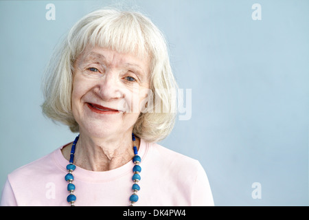 Portrait of senior woman looking at camera in studio - Stock Photo