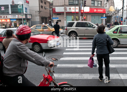 Pedestrian crossing on West Fuxing Road in Shanghai, China. In center: man standing on the middle of the street - Stock Photo