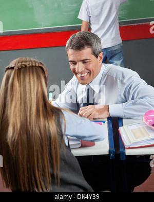 Happy Teacher Teaching Little Girl At Desk - Stock Photo