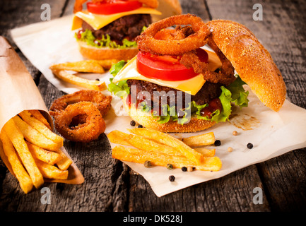 Big burger in bun with onion rings and french fries.Selective focus on the burger - Stock Photo