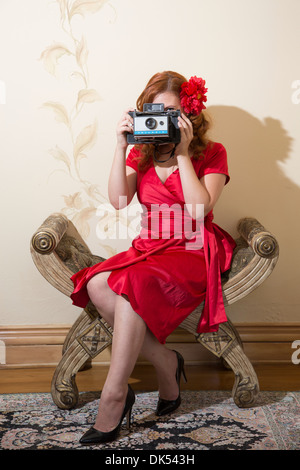 Woman in red dress taking an photograph - Stock Photo