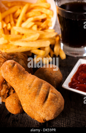 Junk food meal with fried chicken and french fries.Selective focus on the front chicken leg - Stock Photo