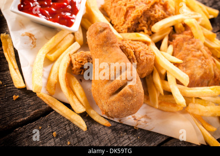 French fries and chicken legs on the wooden table.Selective focus on fried chicken leg in the middle  - Stock Photo