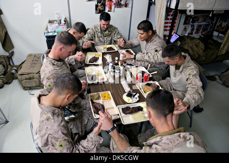 US Marines serving with 3rd Battalion, 7th Marine Regiment's Security Force Advisor Team pray before they enjoy - Stock Photo