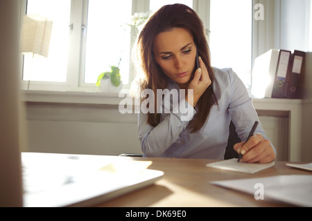 Young woman talking on mobile phone and writing notes while sitting at her desk. Pretty caucasian female working - Stock Photo