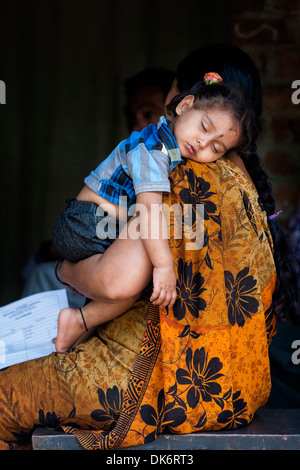 Young Indian baby girl sleeping on her mothers shoulder in a rural Indian village. Andhra Pradesh, India - Stock Photo