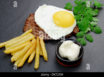 Lucky Steak. Sandwich rump steak topped with a range free fried egg, a side of French fries and mayo. - Stock Photo
