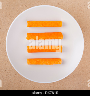 Four crab sticks on plate, over wooden background. - Stock Photo
