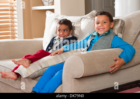 Two boys sitting on a sofa in a living room setting. - Stock Photo
