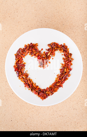 Hot love concept, red chili peppers on plate arranged in heart shape. - Stock Photo