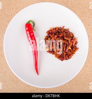 Red chili peppers on plate, over light wooden background. - Stock Photo