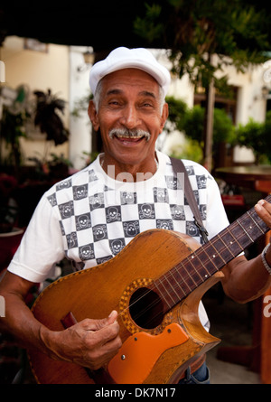 Elderly Cuban musician man playing his guitar in the street, example of local culture, Havana, Cuba, Caribbean - Stock Photo
