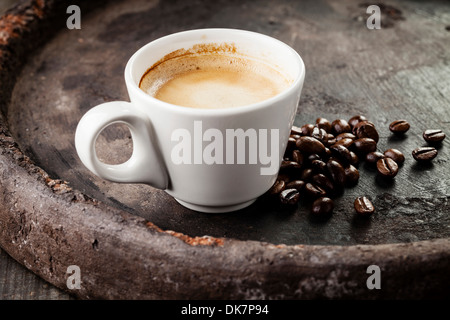 Coffee cup with coffee beans on dark background - Stock Photo