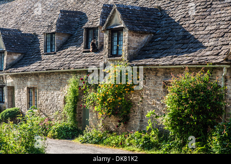 Part of the famous Arlington Row 14th century weavers' cottages in the Cotswold village of Bibury. - Stock Photo