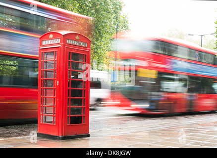 Red Phone cabine and bus in London. Vintage phone cabine monumental - Stock Photo