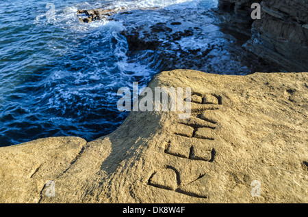 The word REHAB carved into a cliff.  Sunset Cliffs Natural Park, San Diego, California, United States. - Stock Photo