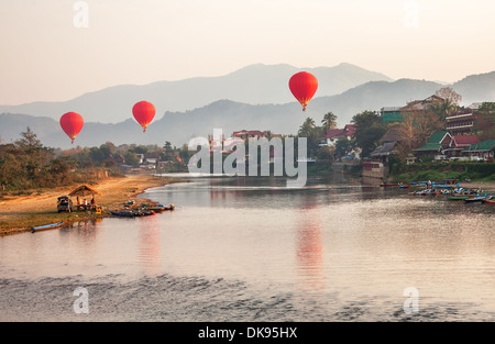 Recreation. Hot air balloons flying over the river Nam Song at sunrise. Vang Vieng, Laos. - Stock Photo