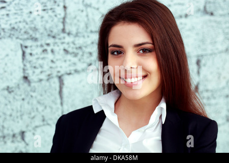 Closeup portrait of a young happy businesswoman near brick wall - Stock Photo