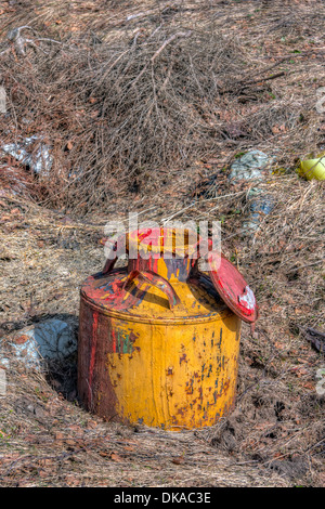 Old forgotten soviet time milk churn covered with paint on the ground - Stock Photo