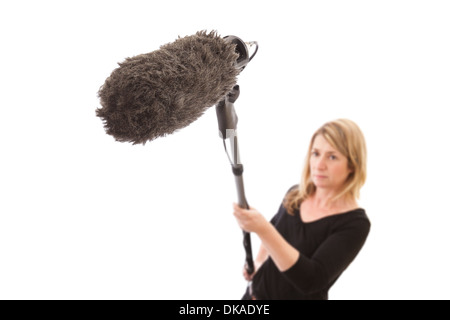 Woman holding a microphone boom against a white background. Selective focus on the furry microphone windshield. - Stock Photo
