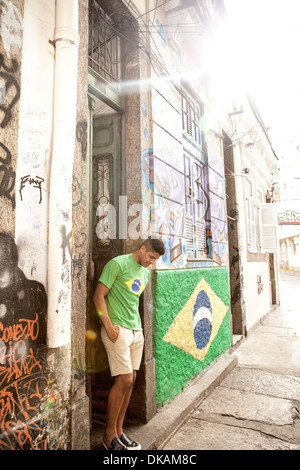 Young man wearing Brazil top standing in doorway next to Brazil flag - Stock Photo