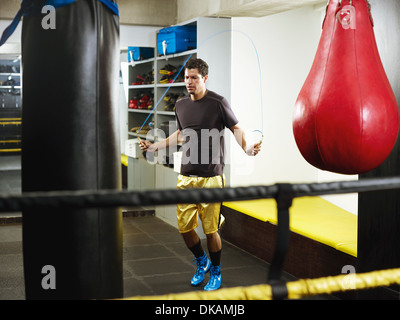 Man skipping to warm up in changing room - Stock Photo
