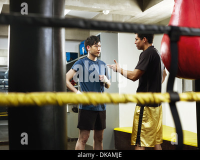 Boxers having conversation in changing room - Stock Photo