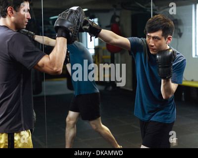 Boxers sparring with gloves and pads - Stock Photo