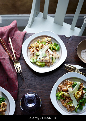Table with cauliflower pasta and parmesan slices - Stock Photo