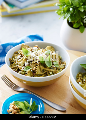 Bowl of farfalle pasta with herb garnish - Stock Photo