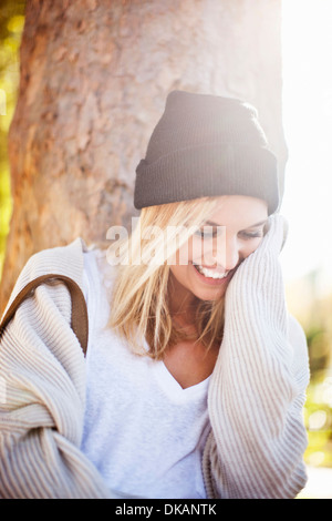 Young woman next to tree trunk in park - Stock Photo