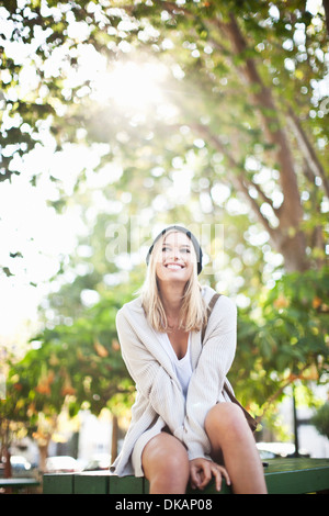 Young woman sitting on bench in park - Stock Photo