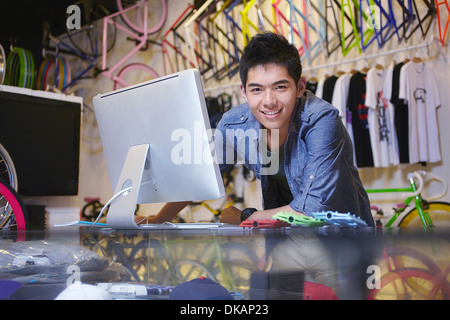 Young man in bike shop using computer - Stock Photo