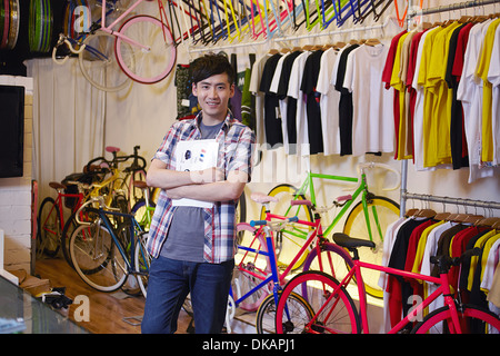 Portrait of young man in bike shop, smiling - Stock Photo