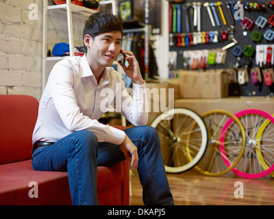 Young man sitting in bike shop on cell phone - Stock Photo