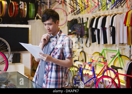 Young man in bike shop holding paperwork - Stock Photo