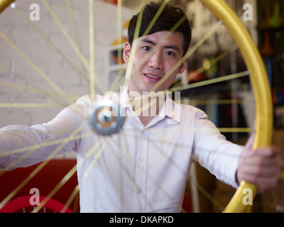 Portrait of young man in bike shop holding bicycle wheel