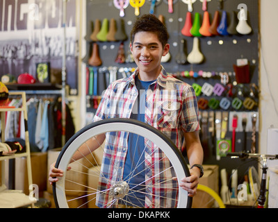 Portrait of young man in bike shop holding bicycle wheel - Stock Photo