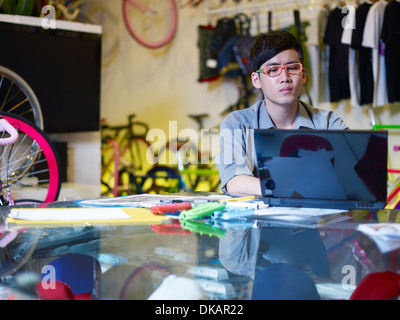 Young man using laptop in bike shop - Stock Photo