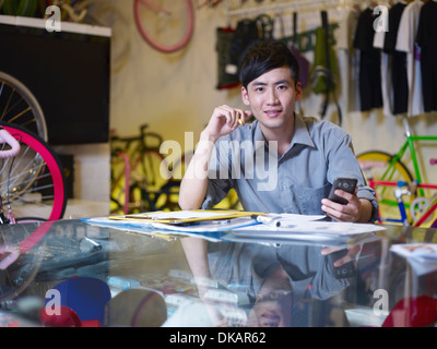 Portrait of young man with cell phone in bike shop - Stock Photo