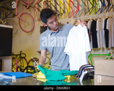 Young man holding t shirts in bike shop - Stock Photo