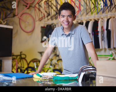 Portrait of young man looking at camera in bike shop - Stock Photo
