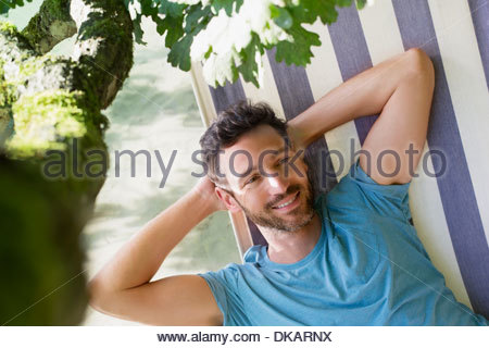 Mature man relaxing in hammock - Stock Photo