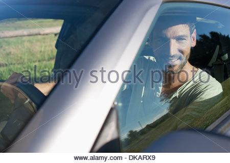 Mature man sitting inside car, smiling - Stock Photo
