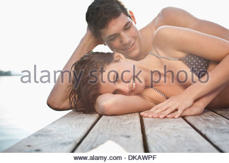 Portrait of young couple lying on side on pier - Stock Photo