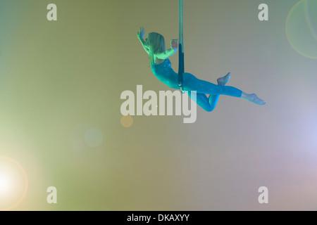 Trapeze artist balancing on trapeze - Stock Photo
