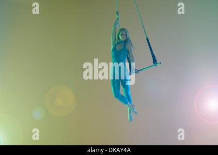 Trapeze artist holding trapeze - Stock Photo