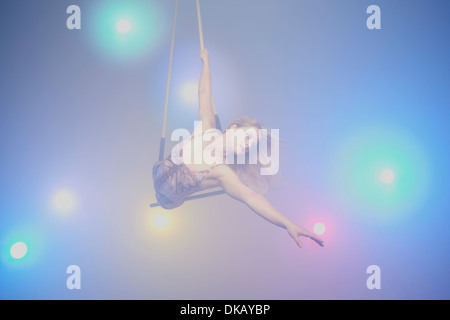 Young woman on trapeze - Stock Photo