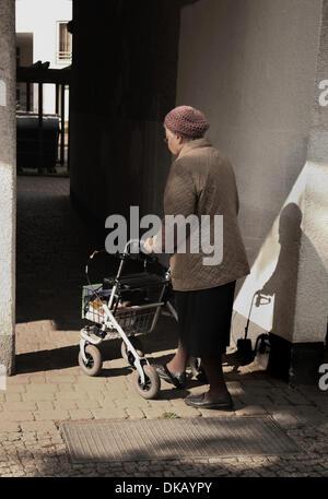 Eine alte Frau geht mit einem Rollator am 01.10.2013 in eine einfache Wohnanlage im Bezirk Wedding in Berlin. Foto: - Stock Photo