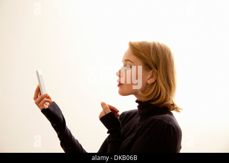 Woman reading message on cellular phone - Stock Photo